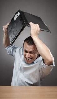 Story Science stock image of a frustrated creative man smashing his laptop on the ground due to rejection